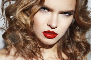 Closeup of the face belong to beautiful young sexy blonde girl with curly hair pure snow white skin and bright makeup red lips, red lipstick, long earrings in emotion.