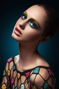Close-up of beautiful female face with colorful make-up.Beauty. Fresh glowing skin. Accessory.Flower.Blue.Art.Theater.Face art.Bright.Closeup.Portrait.Look Fashion make-upt.Fantastic Modern production