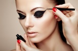 Makeup artist applies eye shadow. Beautiful woman face. Perfect makeup