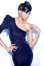 Model posing in dark velvet one-shoulder dress.