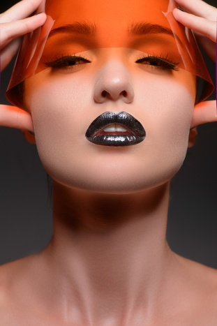 Orange vision. Portrait of beautiful women with closed eyes hold