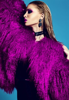 fashion glamor stylish swag young woman model in hipster pink fur coat with bright makeup on blue background